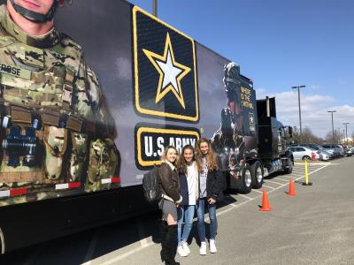 Students pose in front of the Army Demonstration trailer