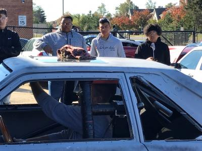 Mr Rollins inside his race car with students watching while he starts the loud engine.
