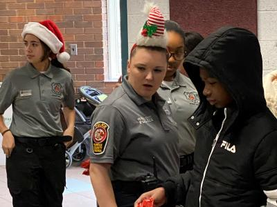 Student volunteers and Police Cadets prepare donated toys for delivery to children.